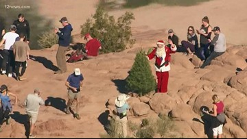 A Grinch tosses the Camelback Christmas tree off the side of the mountain