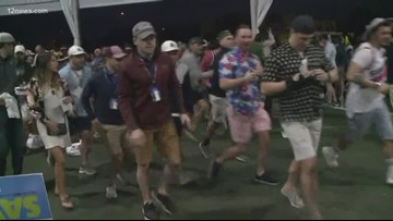 Hundreds of fans run to the 16th hole at the WMPO